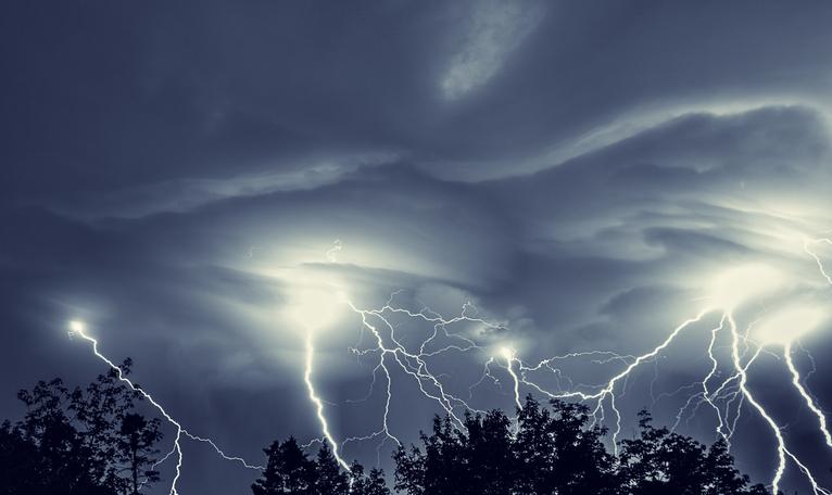 Multiple forks of lightning pierce the night sky.  Long exposure.